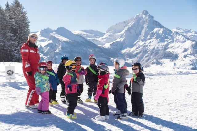 Skischüler mit Skilehrererin im sonnigen Amden