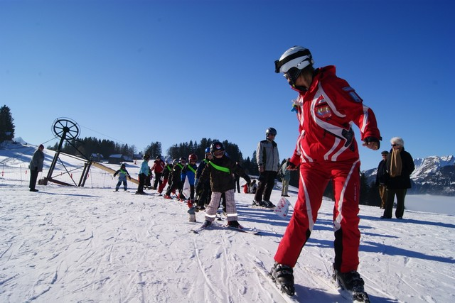 Skilehrer mit Skischülern beim Ponylift im sonnigen Amden