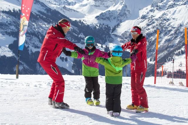 Skischülerinnen mit Skilehrerinnen beim Aufwärmen im sonnigen Amden