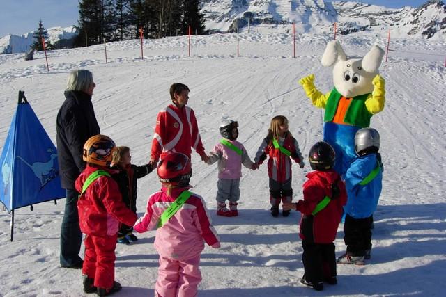 Snowly beim Aufwärmen mit Skischüler im sonnigen Amden